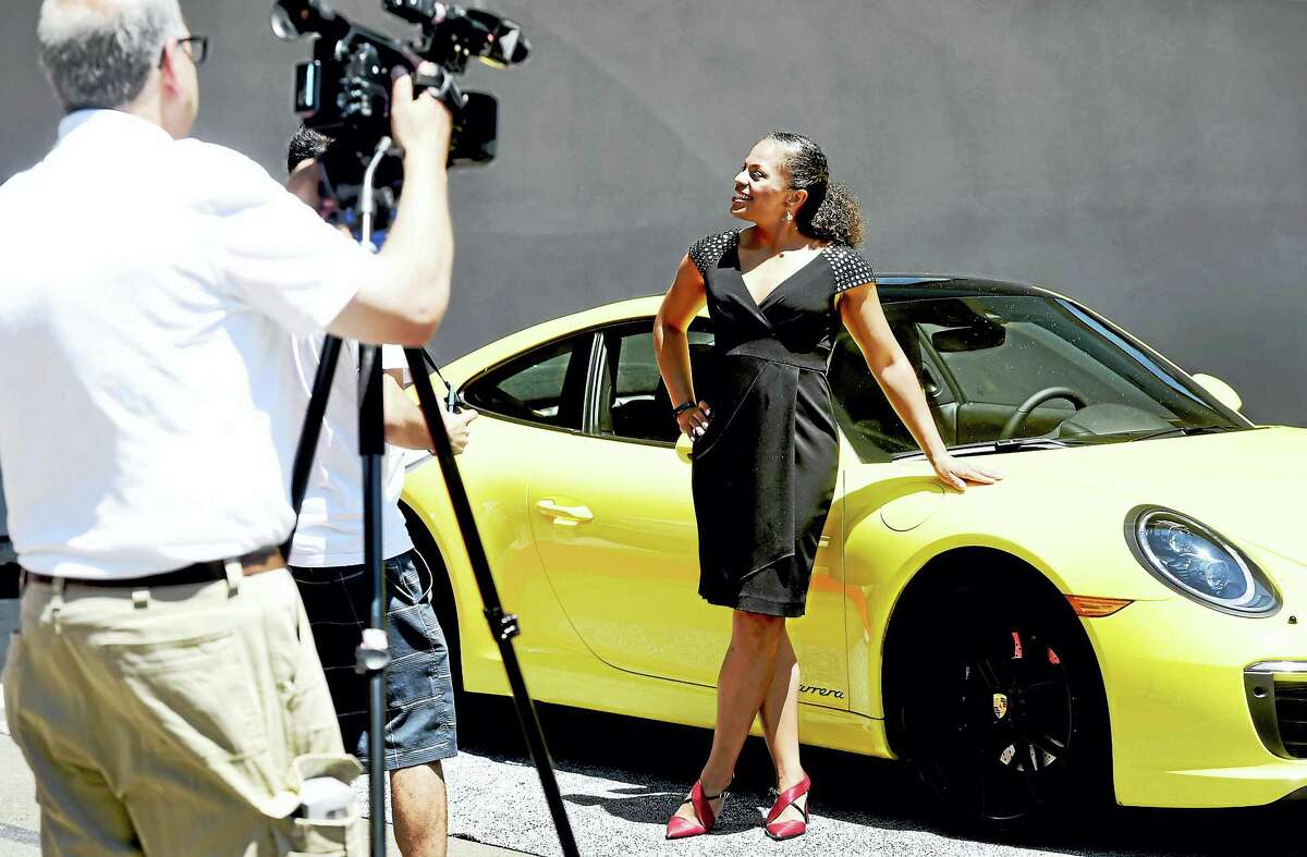 A Porsche sports car stands as a backdrop for Porsche Cars of North America Brand Partner Portfolio Manager Maegan Moguel during the Connecticut Open media day on Wednesday. Porsche has signed on as one of the sponsors of the event.