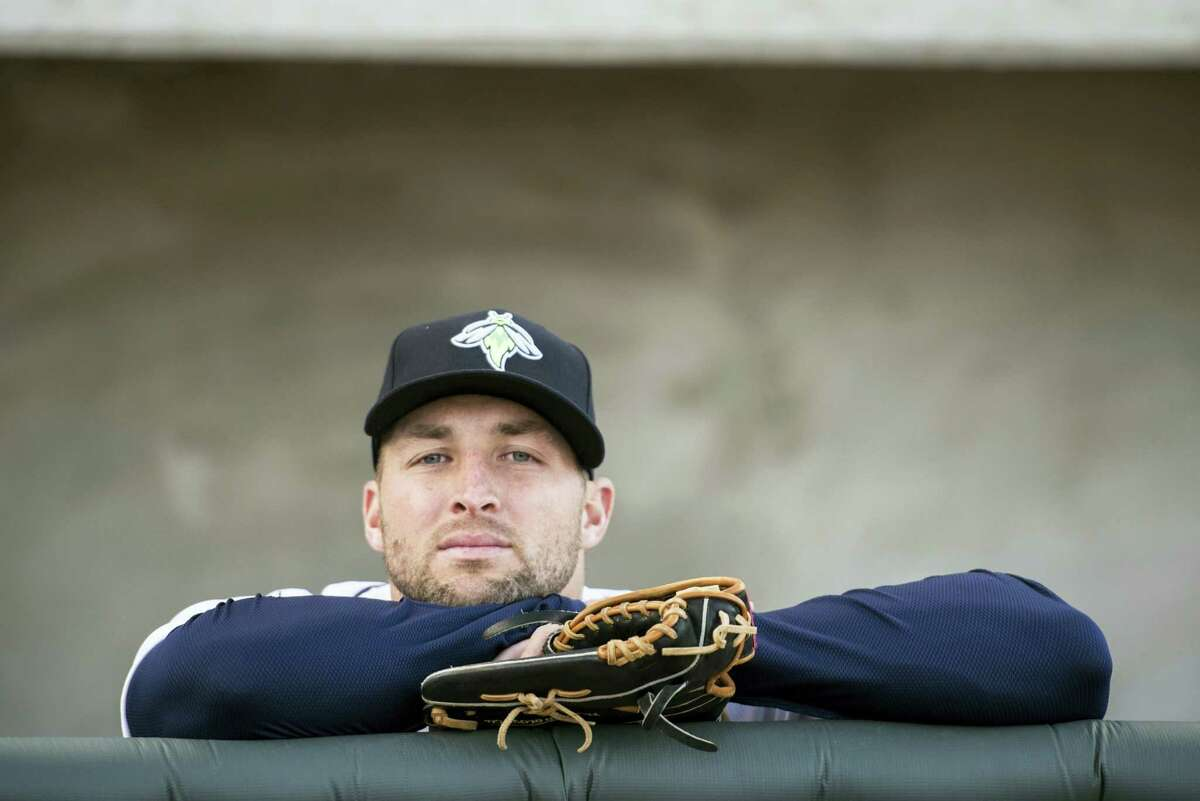 Tim Tebow looks out from the dugout.