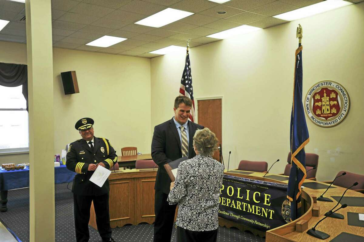 Officer Justin Waltzer is recognized by Winsted Town Clerk Sheila Sedlak during the swearing-in ceremony.