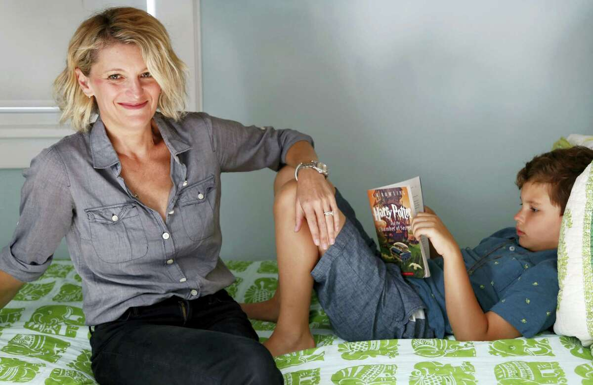 """Theo Galkin, 8, rereads a favorite part of """"Harry Potter and the Sorcerer's Stone"""" while posing for a picture with his mother Chloe Galkin at their home in South Orange, N.J., Wednesday, June 28, 2017. As the 20th anniversary of the initial publishing of the first Harry Potter book is celebrated this week, another generation is being introduced to Harry, Hogwarts and all the rest of the magical world created by author J.K. Rowling."""