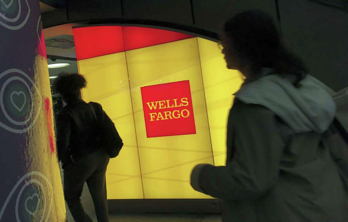 In this Thursday, Oct. 13, 2016, file photo, commuters walk by a Wells Fargo ATM location at New York's Penn Station. On Wednesday, June 28, 2017, the Federal Reserve gave the green light to all 34 of the biggest banks in the U.S. to raise their dividends and buy back shares, judging their financial foundations sturdy enough to withstand a major economic downturn. Those allowed to raise dividends or repurchase shares include the four biggest U.S. banks: JPMorgan Chase, Bank of America, Citigroup and Wells Fargo.