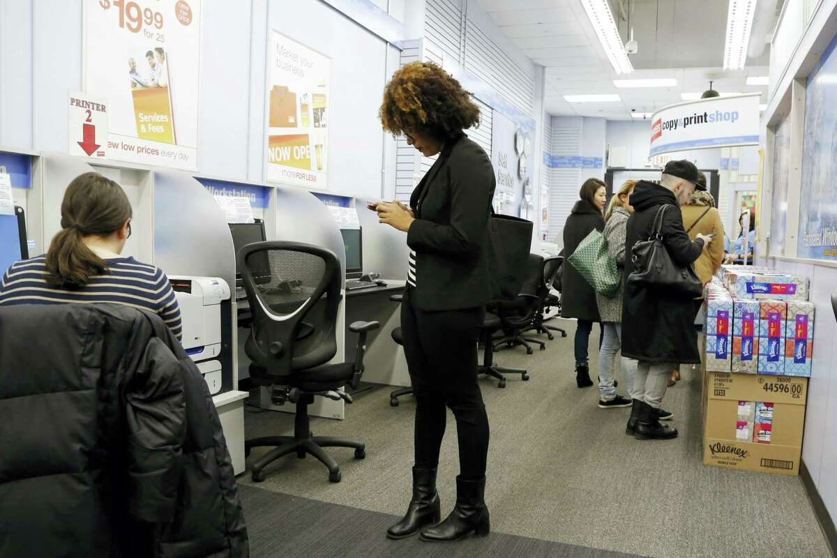 In this Tuesday, March 1, 2016, file photo, customers work in a Staples copy & print shop in New York. On Wednesday, June 28, 2017, private equity firm Sycamore announced it is buying office supplies chain Staples for $6.9 billion.