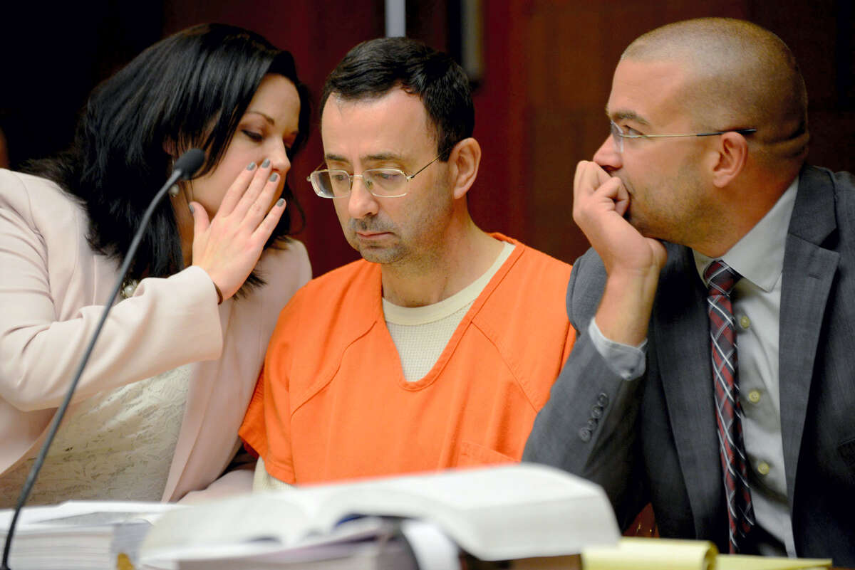 In this May 26, 2017 photo, defense attorney Shannon Smith talks to her client, Dr. Larry Nassar, during the second portion of his preliminary hearing on sexual assault at the 55th District Court in Mason, Mich. USA Gymnastics needs to undergo a 'complete cultural change' to become better equipped at protecting athletes from abuse according to an independent review of the embattled organization's practices. USA Gymnastics ordered the review last fall following a series of civil of lawsuits filed against the organization and the former team doctor by a pair of gymnasts who claim the physician sexually abused them during their time on the U.S. national team.