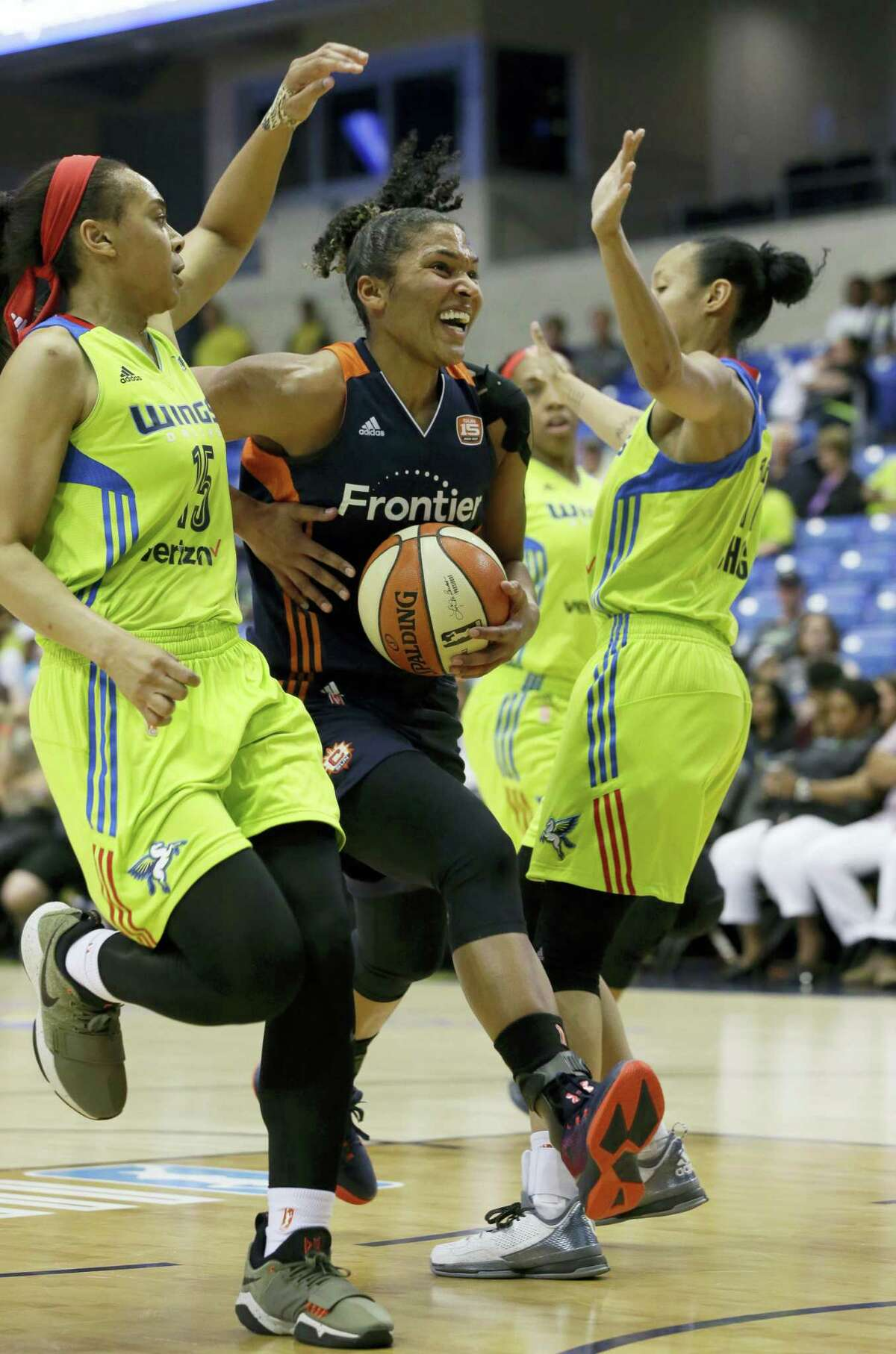 Connecticut Sun forward Alyssa Thomas, center, tries to drive against Dallas Wings defenders Allisha Gray (15) and Saniya Chong (12) during the second half of a WNBA basketball game in Arlington, Texas on June 25, 2017.