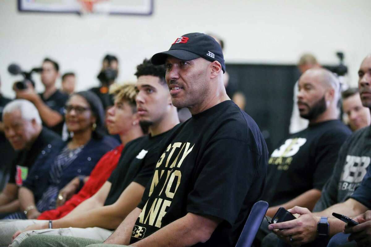 """In this June 23, 2017 photo, LaVar Ball, center, father of Los Angeles Lakers draft pick Lonzo Ball, listens to his son during the NBA basketball team's news conference in El Segundo, Calif. LaVar and Lonzo appeared on """"WWE Raw"""" June 26, 2017."""