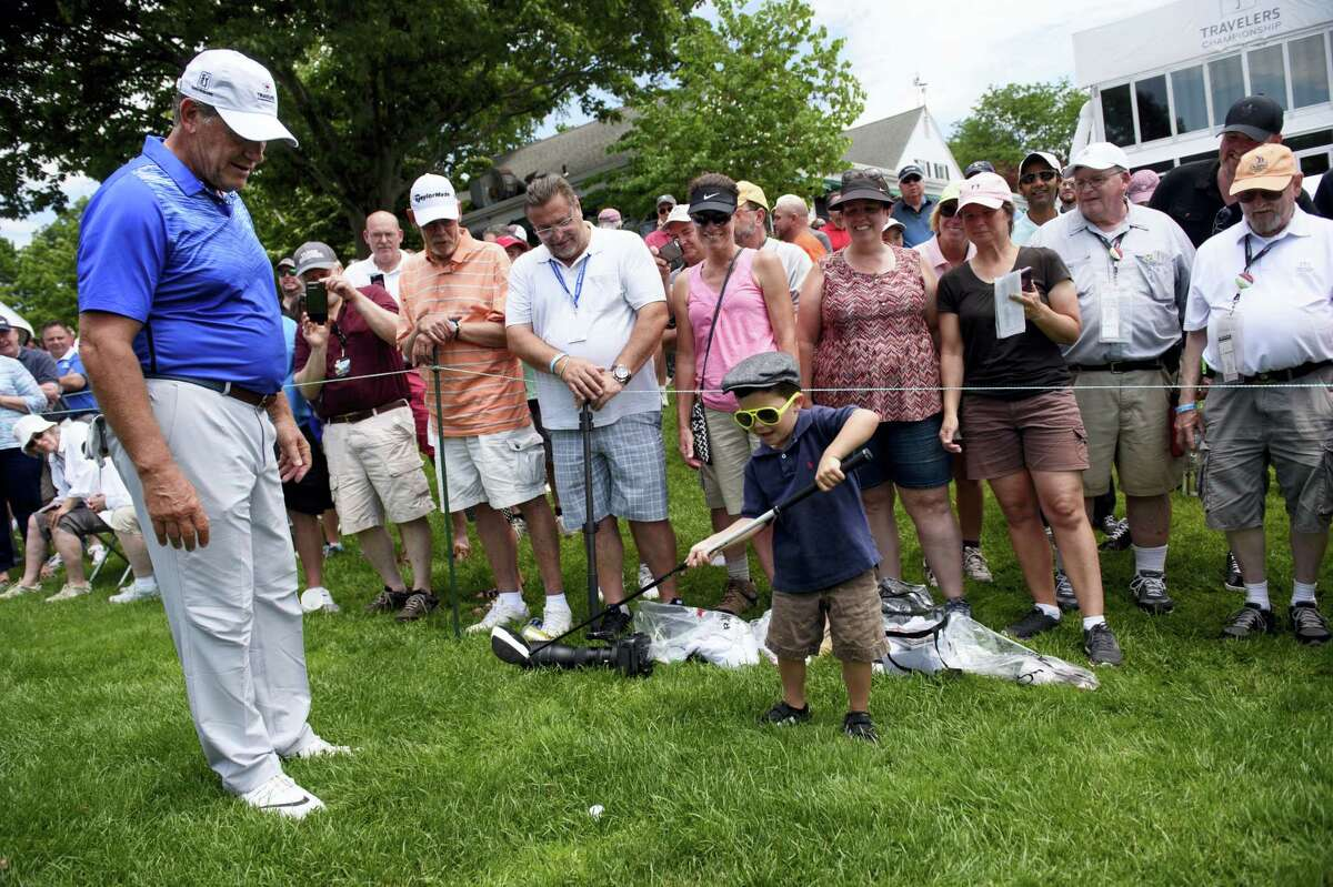 UConn women's basketball coach Geno Auriemma, left, watches Jake Ragan, 5, try to swing Auriemma's driver before he teed-off on the first hole at the Travelers Championship Celebrity Pro-Am at TPC River Highlands last Wednesday.