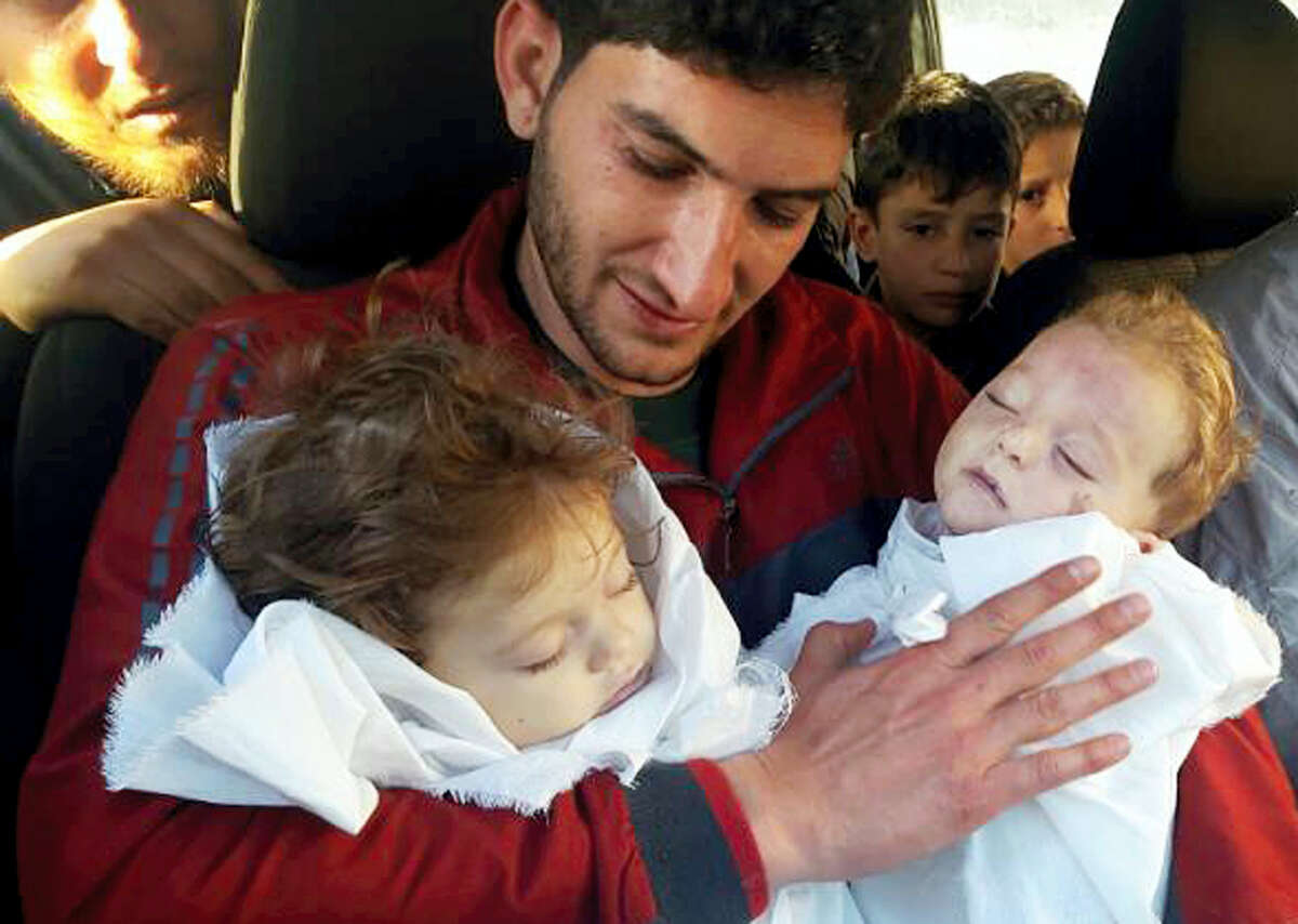 FILE -In this fie picture taken on Tuesday April 4, 2017, Abdul-Hamid Alyousef, 29, holds his twin babies who were killed during a suspected chemical weapons attack, in Khan Sheikhoun in the northern province of Idlib, Syria. The Syrian government on Tuesday, June 27, 2017 dismissed White House allegations that it was preparing a new chemical weapons attack, as activists reported an airstrike on an Islamic State-run jail in eastern Syria that they said killed more than 40 prisoners.