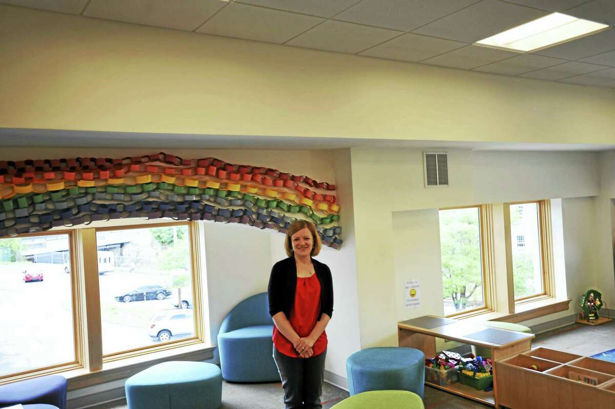 The Children's Room at the Torrington Public Library, here featuring library Executive Director Jessica Gueniat. A mural is planned to line the room on the white space between the ceiling and the rainbow depicted above.