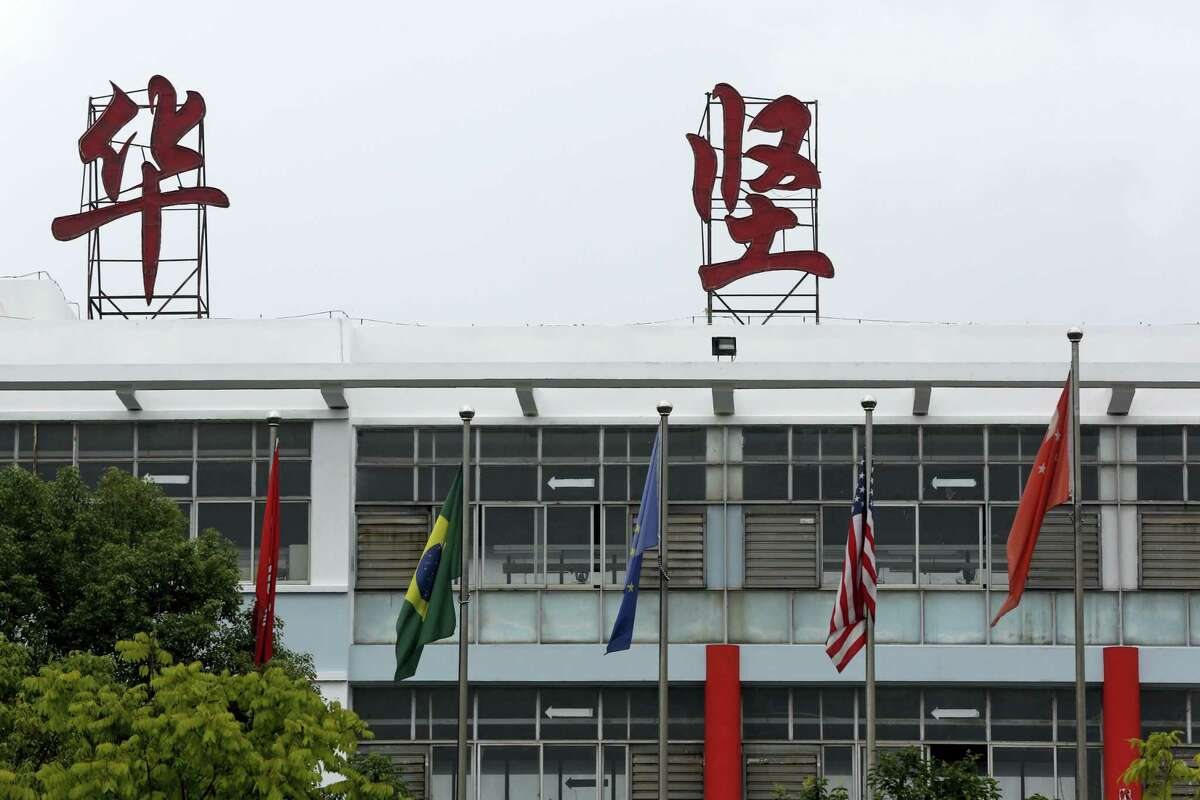 In this June 18, 2017, photo, Chinese, American and other international flags stand at the factory of Ganzhou Huajian International Shoe City Co., which has made shoes for the Ivanka Trump brand, in Ganzhou in southern China's Jiangxi Province. Chinese who have worked at the factory, that also makes shoes for other brands, say they've faced 16-hour days, low pay and verbal abuse. The Chinese words, seen on top, read Huajian.
