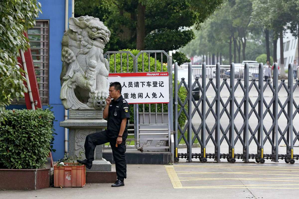 """In this June 18, 2017, photo, a security guard smokes near a main entrance gate of the Ganzhou Huajian International Shoe City Co.'s factory, which has made shoes for the Ivanka Trump brand, in Ganzhou in southern China's Jiangxi Province. The sign reads """"visitors please exit the vehicle and register, people without relevant reasons cannot enter this important factory area."""" (AP Photo/Andy Wong)"""