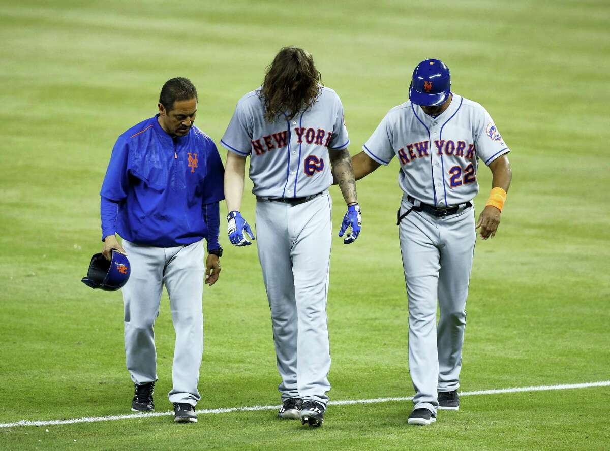 New York Mets' Robert Gsellman (65) is helped off the field by first base coach Tom Goodwin (22) and a trainer during the fourth inning of a baseball game against the Miami Marlins, Tuesday. Gsellman grabbed the back of his left thigh as he approached first base and grimaced in pain. He was replaced on the mound by Paul Sewald in the bottom of the fourth inning.