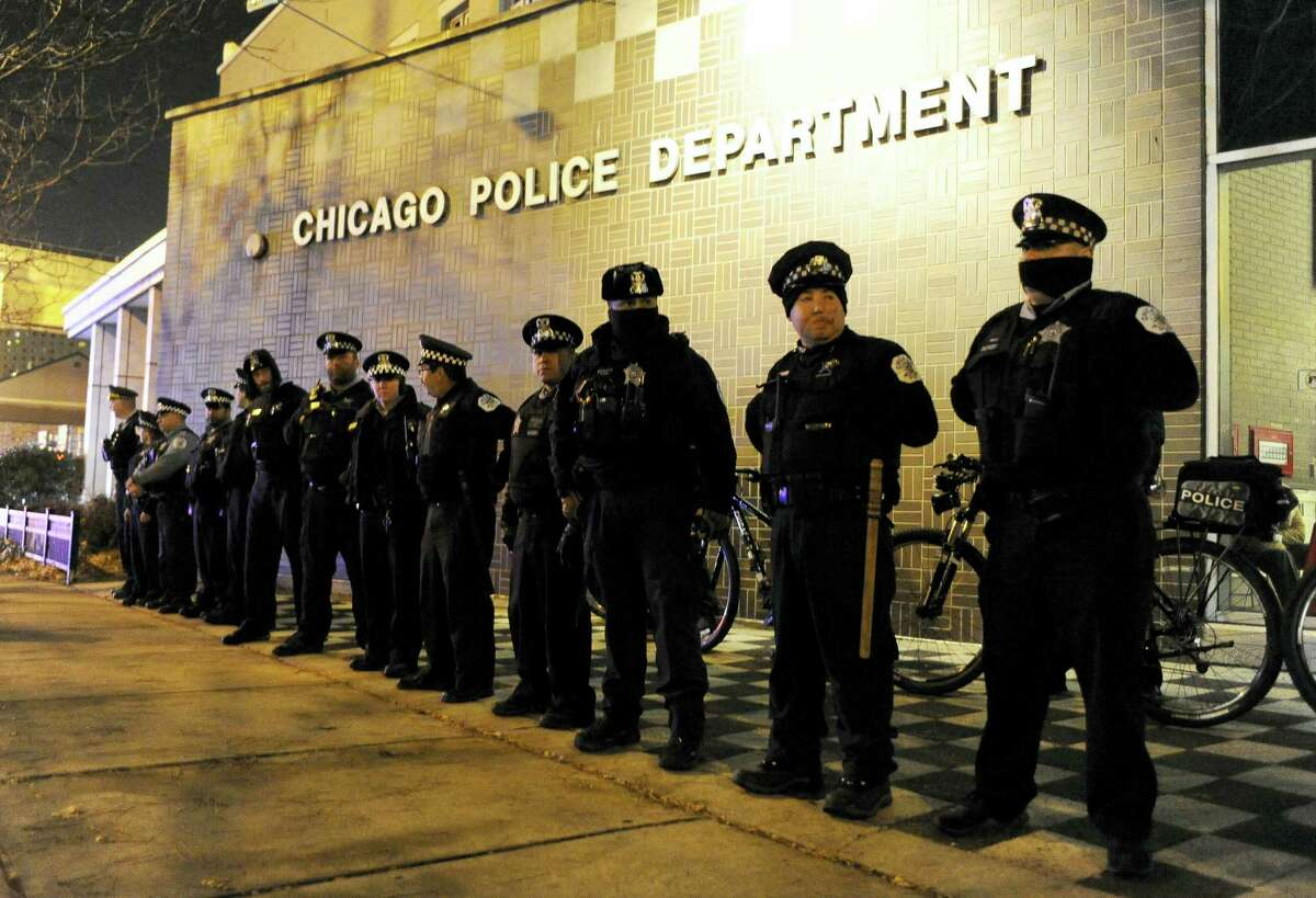 In this Nov. 24, 2015, file photo, Chicago police officers line up outside the District 1 central headquarters in Chicago, during a protest for the fatal police shooting of 17-year-old Laquan McDonald. Special prosecutor Patricia Brown-Holmes announced Tuesday, June 27, 2017, that three Chicago police officers were indicted on felony charges that they conspired to cover up the actions of Chicago Police Officer Jason Van Dyke in the killing of McDonald. The indictment, approved by a Cook County grand jury, alleges that one current and two former officers lied about the events of Oct. 20, 2014 when Van Dyke shot the black teenager 16 times.