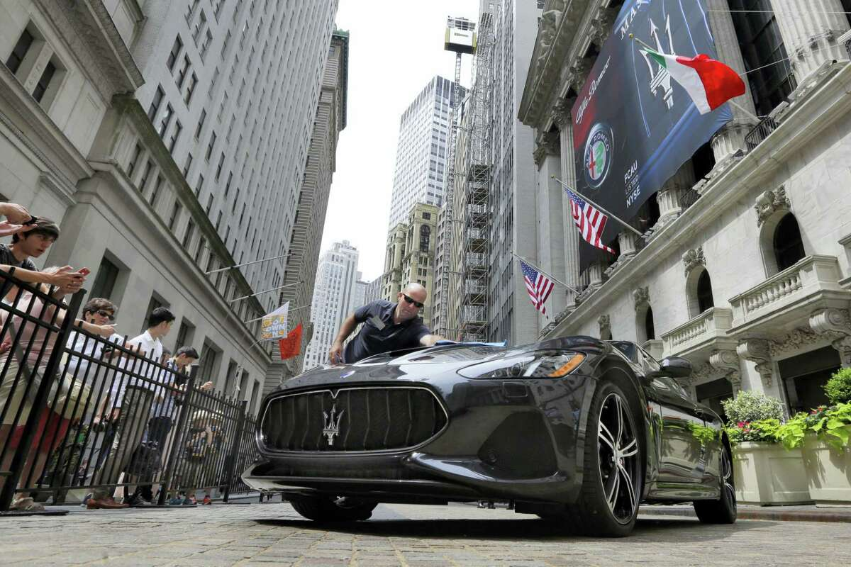 A worker from Fiat Chrysler Automobiles cleans a Maserati GranTurismo MC on display in front of the New York Stock Exchange, Tuesday, June 27, 2017.