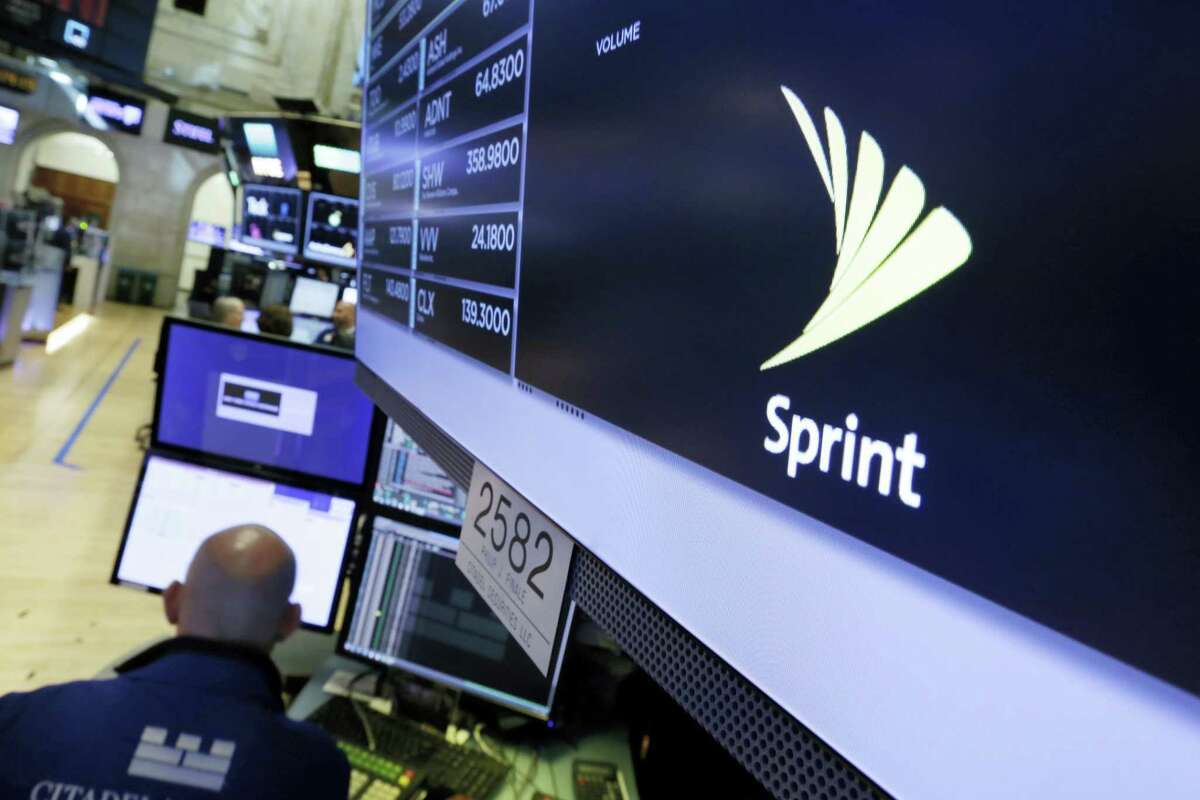 The Sprint logo appears above a trading post on the floor of the New York Stock Exchange, Tuesday, June 27, 2017. Sprint climbed 5.8 percent following a published report suggesting the mobile phone company is in talks with Charter Communications and Comcast Corp. on a deal that could enable the cable operators to buy a stake in Sprint. (AP Photo/Richard Drew)