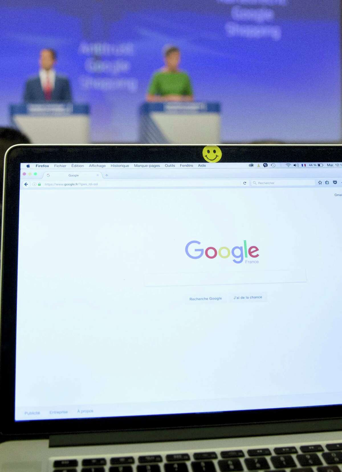 A Google search site is open on the computer of a journalist during a media conference of European Union Commissioner for Competition Margrethe Vestager, right rear, at EU headquarters in Brussels on Tuesday, June 27, 2017. The European Union's competition watchdog has fined internet giant Google over its online shopping service.