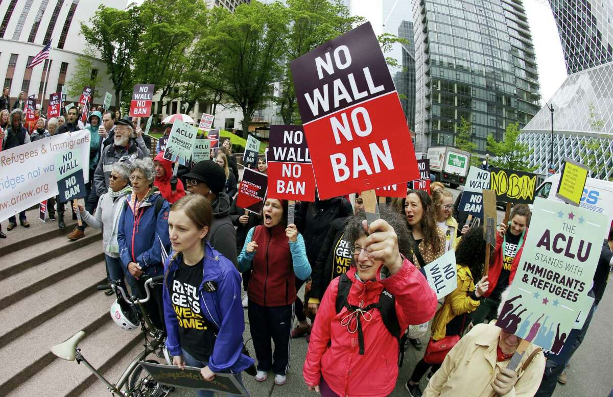 In this May 15, 2017 photo, protesters wave signs and chant during a demonstration against President Donald Trump's revised travel ban, outside a federal courthouse in Seattle. The Supreme Court is letting the Trump administration enforce its 90-day ban on travelers from six mostly Muslim countries, overturning lower court orders that blocked it.