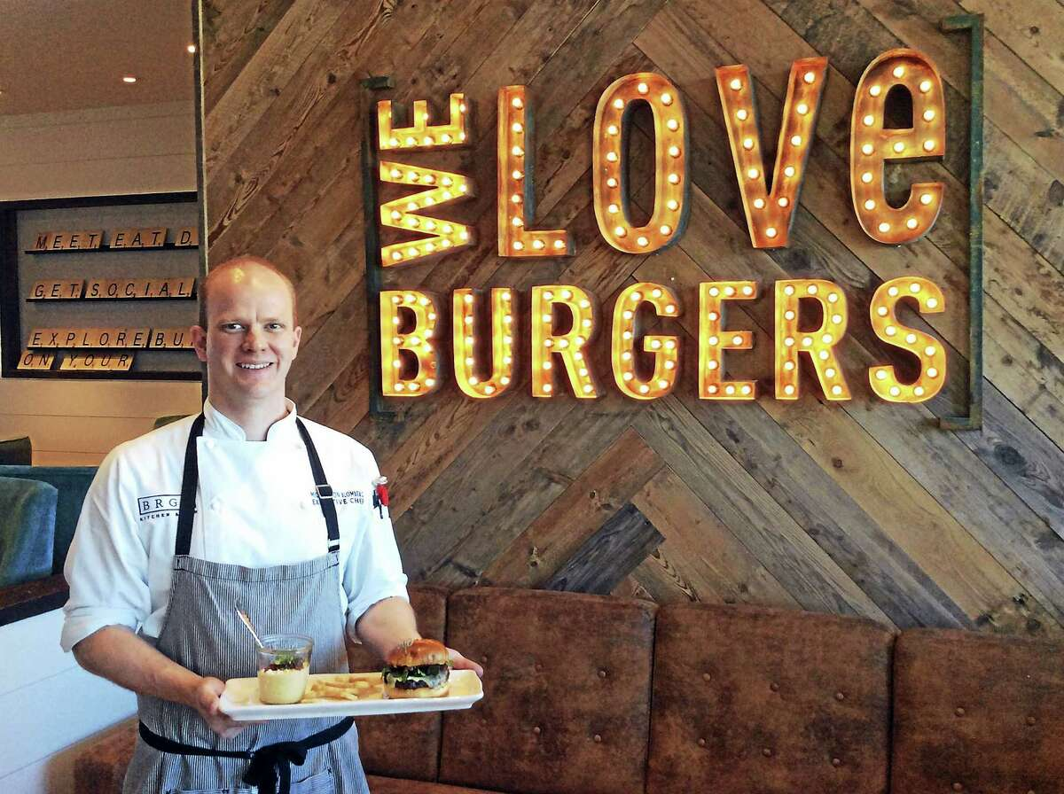Michael von Blomberg, director of food and beverage and executive chef at Treasure Island Beach Resort, stands with a signature burger, white bean spread and bourbon bacon jam.