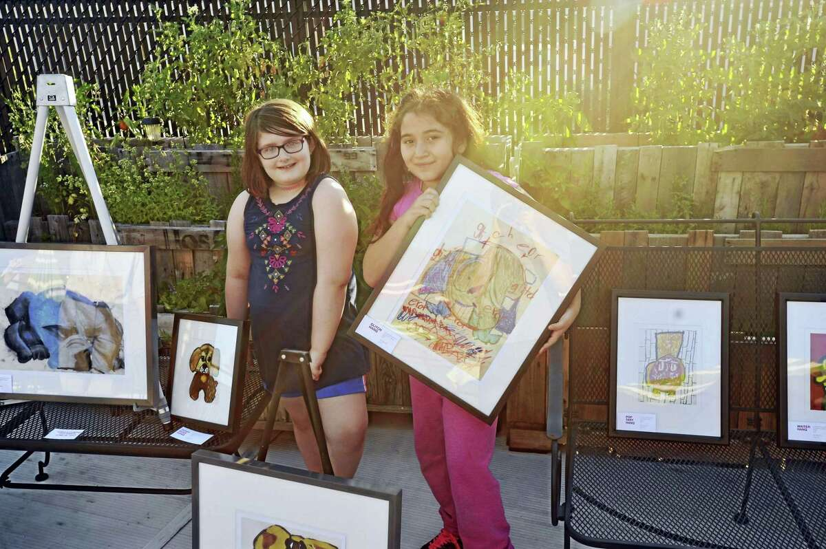 Students from CAFTA put their artwork on display Monday, as a fundraiser was held at Hanq's in Torrington to benefit the organization and the Susan B. Anthony Project. Above, Mariee Townsend and Daniela Penaranda pose with their visions of Hanq.