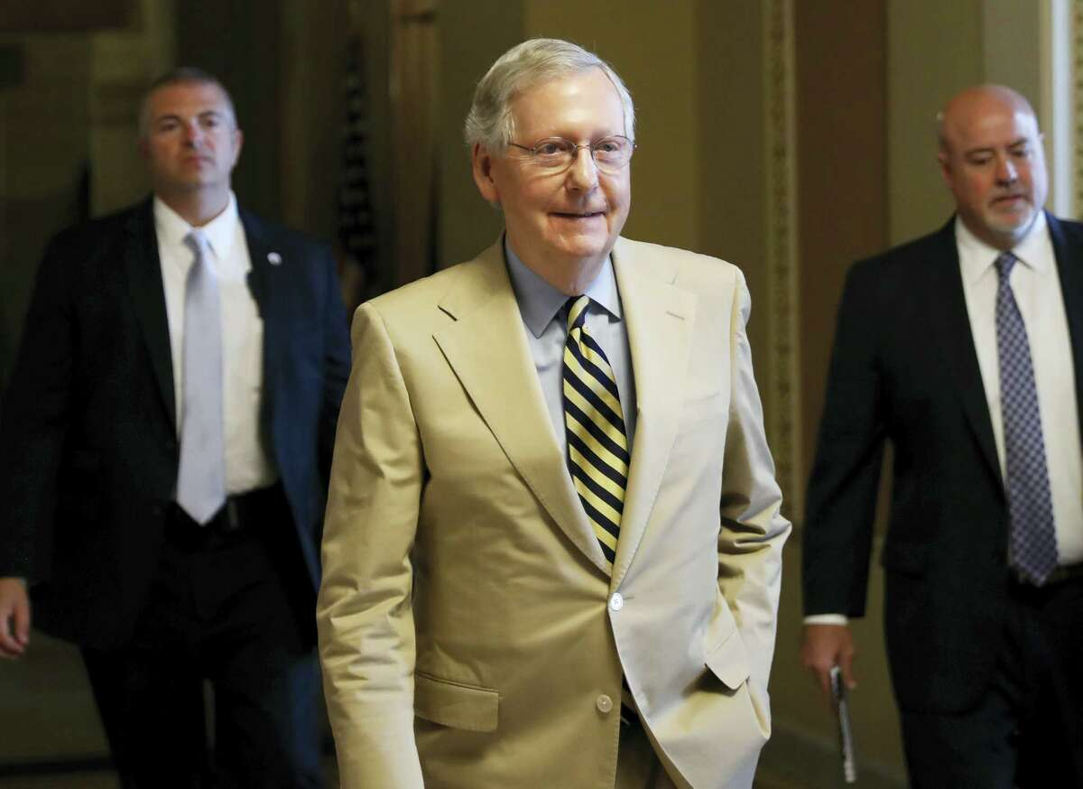 """Senate Majority Leader Mitch McConnell of Ky. walks from his office on Capitol Hill in Washington, June 26. Senate Republicans unveil a revised health care bill in hopes of securing support from wavering GOP lawmakers, including one who calls the drive to whip his party's bill through the Senate this week """"a little offensive."""""""