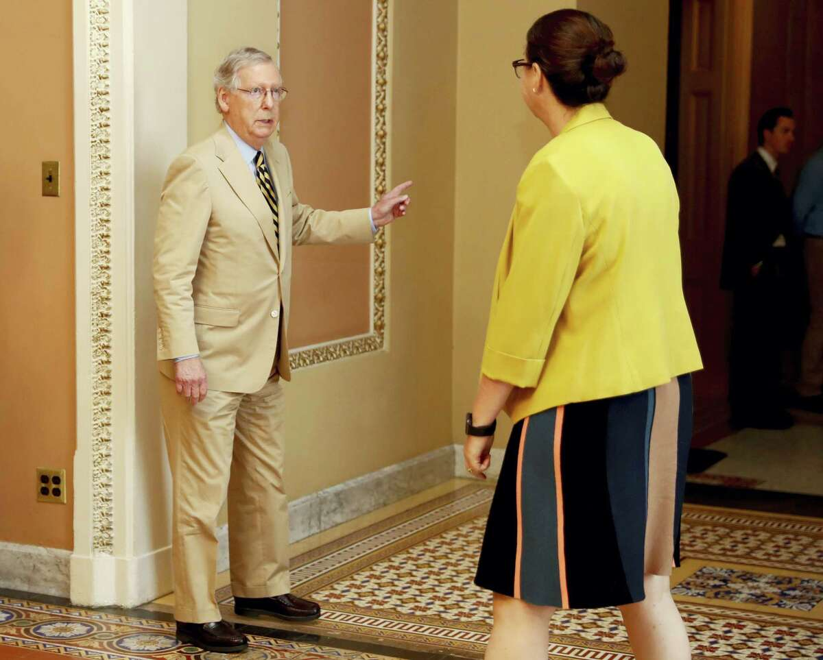 """Senate Majority Leader Mitch McConnell of Ky., talks with Secretary for the Majority Laura Dove, as he walks to his office on Capitol Hill in Washington, June 26. Senate Republicans unveil a revised health care bill in hopes of securing support from wavering GOP lawmakers, including one who calls the drive to whip his party's bill through the Senate this week """"a little offensive."""""""