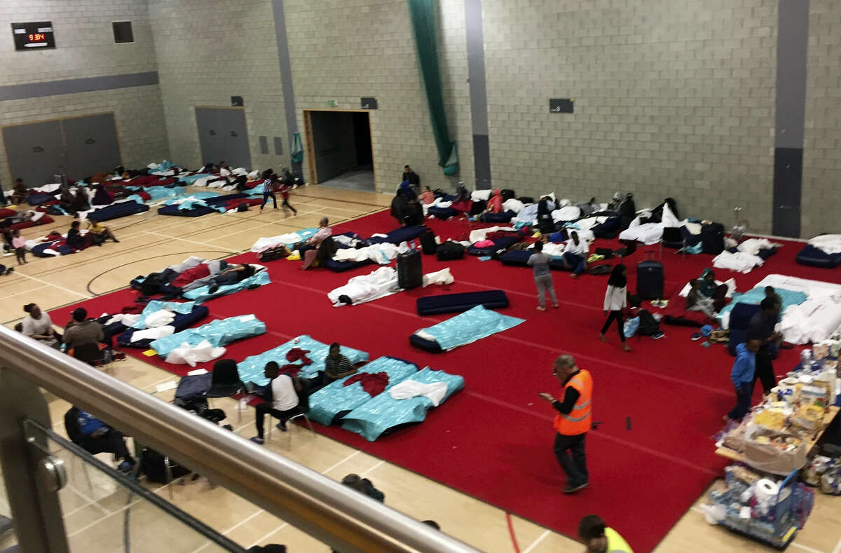 People gather in a leisure centre in Swiss Cottage, north London, Saturday June 24, 2017, after the local council evacuated some 650 homes overnight. Camden Borough Council said in a statement Saturday that it housed many of the residents at two temporary shelters while many others were provided hotel rooms, after inspectors found fire safety issues in housing towers, following the inferno in a west London apartment block that killed 79.