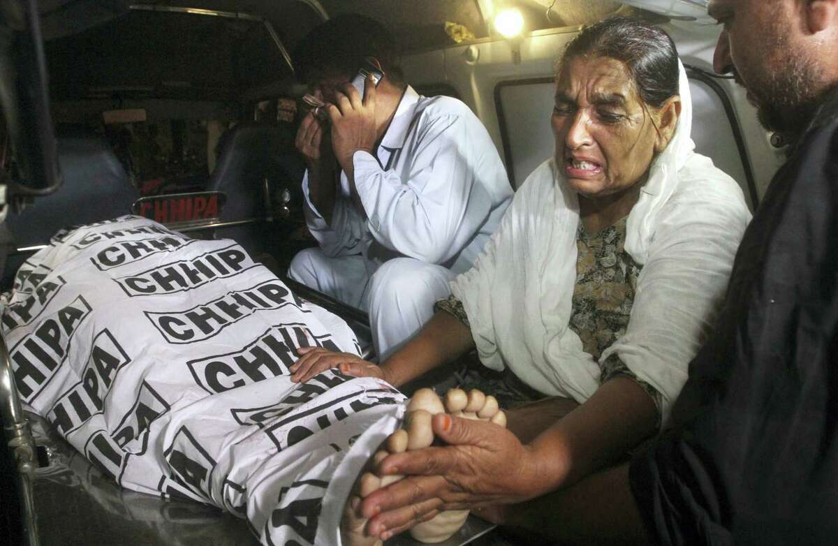 Mother of a police officer, who was killed by gunmen, mourns next to her son's body, carried into an ambulance at a hospital in Karachi, Pakistan, late Friday, June 23, 2017. Gunmen in the port city attacked police officers at a roadside restaurant and killed four of them before fleeing, according to senior police officer Asif Ahmed.