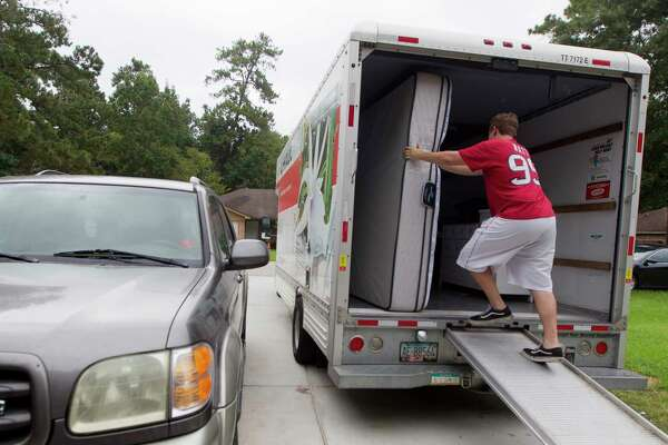 Dylan Cyr moves a mattress to a U-Haul as his family moves items from their home in the Timber Lakes-Timber Ridge subdivision to a relative?•s house in The Woodlands, Friday, Aug. 25, 2017, in Spring.