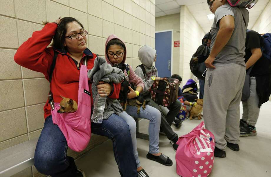 Lucia Ortiz (left) and her daughter Alexis wait with the pet dogs for a bus to evacuate them from Corpus Christi to San Antonio on Friday, Aug. 25, 2017. Some Corpus Christi residents opting to leave the city gathered at the Corpus Christi Gymnasium where they were registered and prepared to take a trip to San Antonio on Friday. As Hurricane Harvey grew to Category 2 hurricane status, the city urged residents to evacuate. One option was to be taken by buses from the gymnasium and taken to a shelter in San Antonio. (Kin Man Hui/San Antonio Express-News) Photo: Kin Man Hui, Staff / San Antonio Express-News / ©2017 San Antonio Express-News