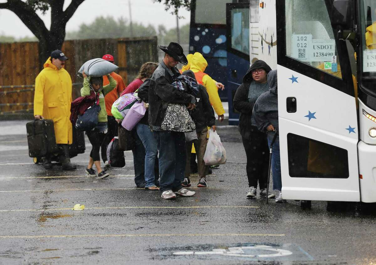 Corpus Christi residents prepare to board a bus as they evacuate and head for San Antonio. At the Corpus Christi Gym, the evacuation staging area, families registered and were given bar codes, a safety precaution to ensure accountability that was developed by the Federal Emergency Management Agency.