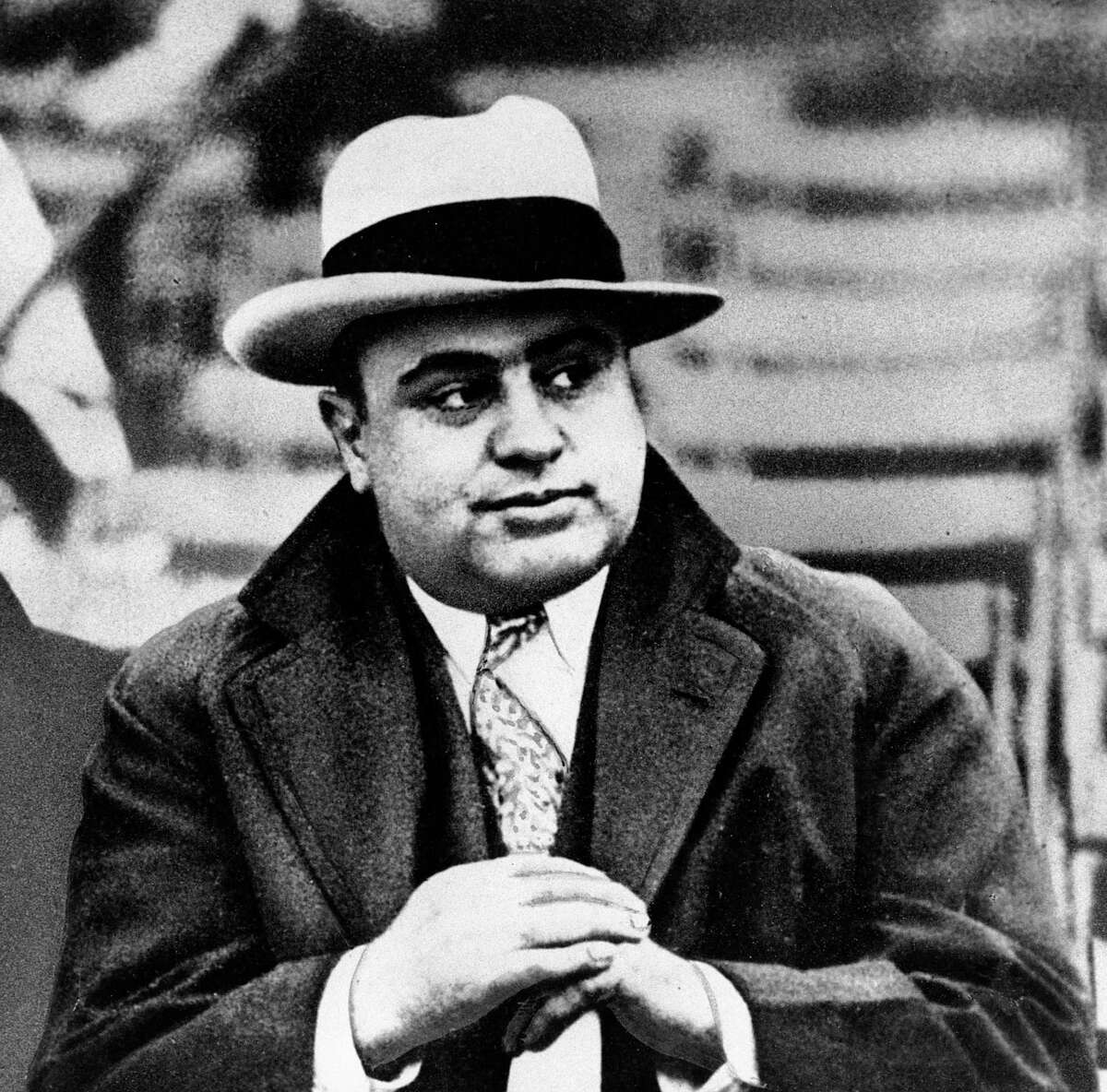 """In this Jan. 19, 1931 file photograph, Chicago mobster Al Capone is seen at a football game in Chicago. Artifacts connected to some of the nation's most notorious gangsters are being auctioned this weekend. A handwritten musical composition by Al Capone, a letter written by a jailed John Gotti asking someone to """"keep the martinis cold,"""" and jewelry that belonged to Bonnie and Clyde are among the items up for bid Saturday in the """"Gangsters, Outlaws and Lawmen"""" auction in Cambridge, Mass."""