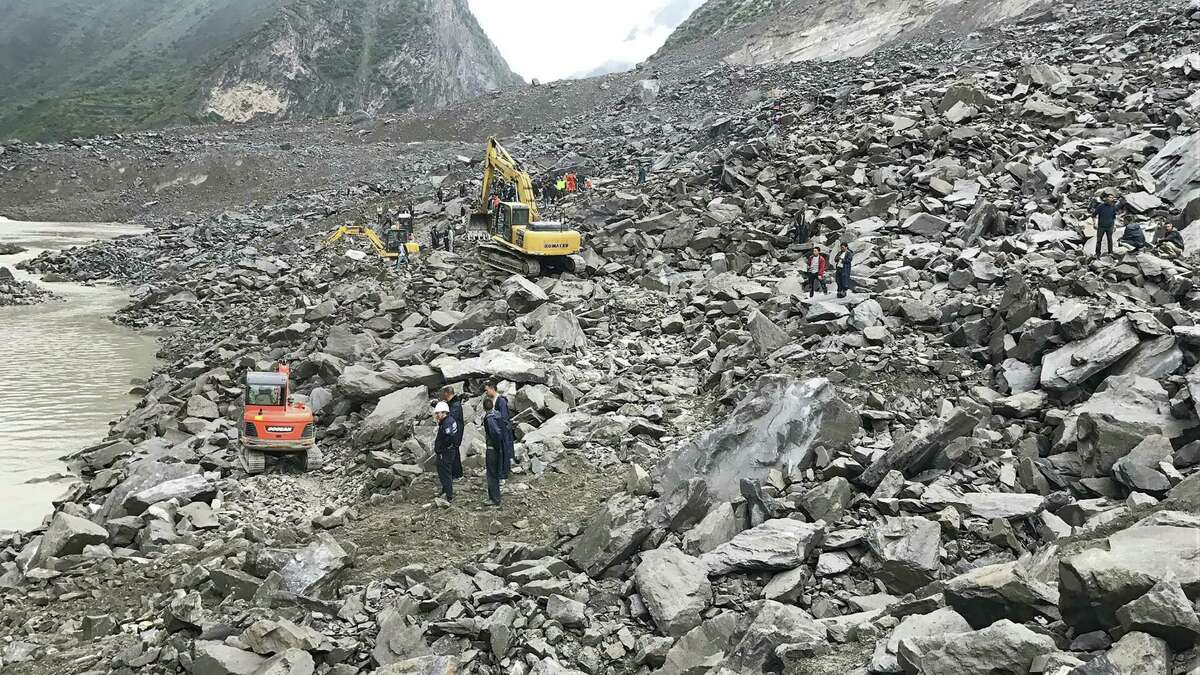 Emergency personnel and earthmoving equipment work at the site of a massive landslide in Xinmo village in Maoxian County in southwestern China's Sichuan Province, Saturday, June 24, 2017. Dozens of people are feared buried by a landslide that unleashed huge rocks and a mass of earth that crashed into their homes in southwestern China early Saturday, a county government said.