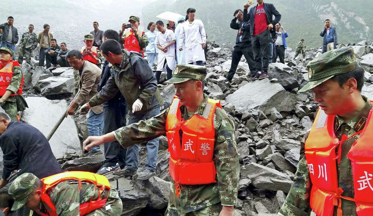 Emergency personnel and local people work at the site of a landslide in Xinmo village in Maoxian County in southwestern China's Sichuan Province, Saturday, June 24, 2017. Dozens of people are feared buried by a landslide that unleashed huge rocks and a mass of earth that crashed into their homes in southwestern China early Saturday, a county government said.(Chinatopix via AP)