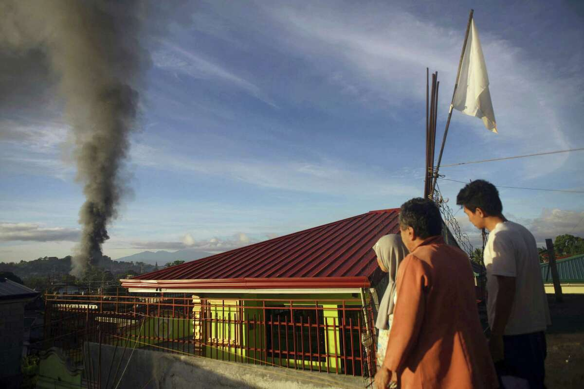 A resident looks at a burning structure during early morning airstrikes by government forces in the continuing fight for Marawi city by Muslim militants Friday, June 23, 2017, in southern Philippines. The siege by militants aligned with the Islamic State group continues as it enters its second month Friday.