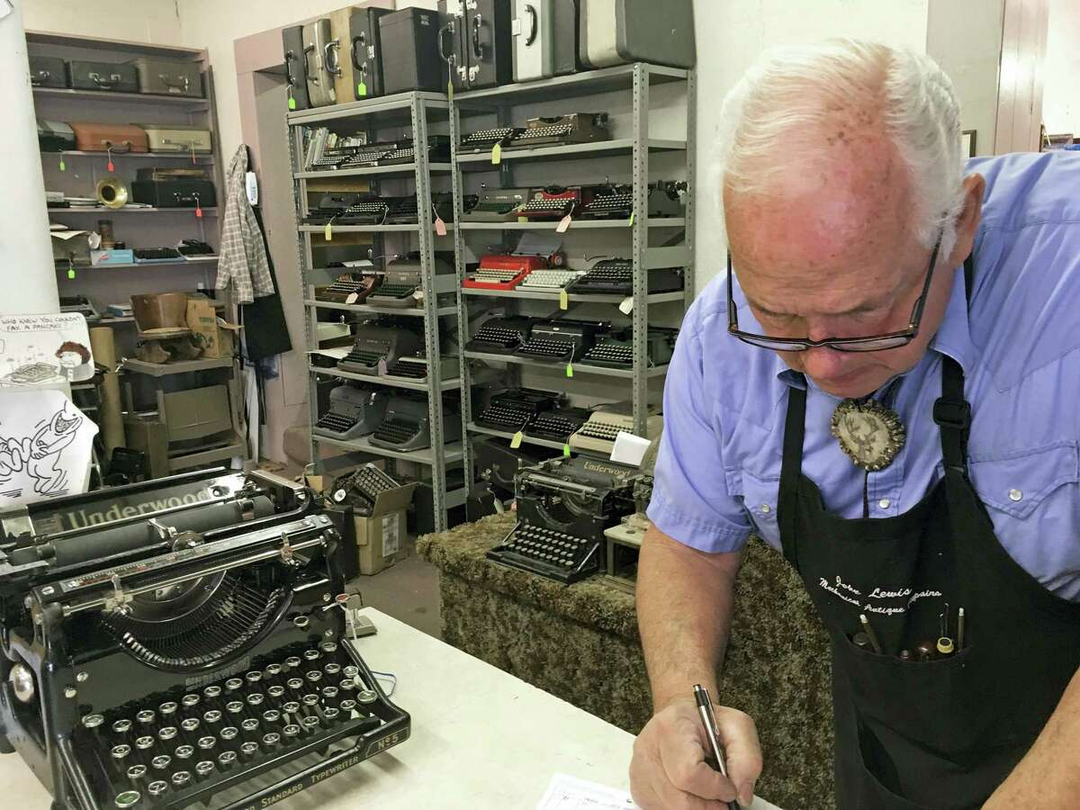John Lewis, a typewriter repairman, works at his shop in Albuquerque, N.M., in front of his collection of vintage typewriters.