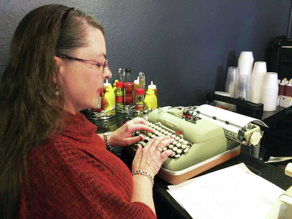 """Andrea Kittle, of Albuquerque, N.M., tries out a vintage Smith Corona electric typewriter at a """"type-in"""" in Albuquerque. """"Type-ins"""" are social gatherings in public places where typewriter fans test different vintage machines."""