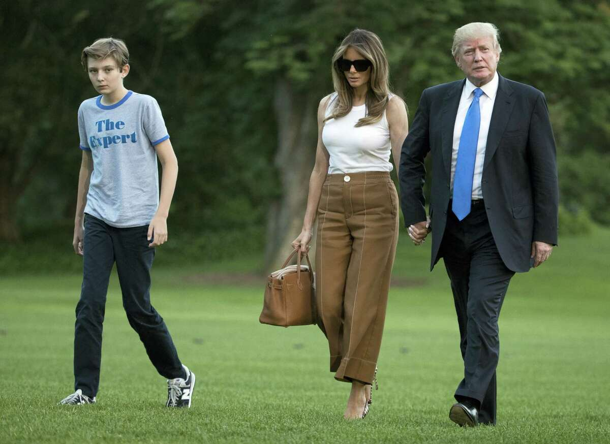 President Donald Trump, first lady Melania Trump, and their son and Barron Trump walk from Marine One across the South Lawn to the White House in Washington, Sunday, June 11, 2017, as they return from Bedminster, N.J.
