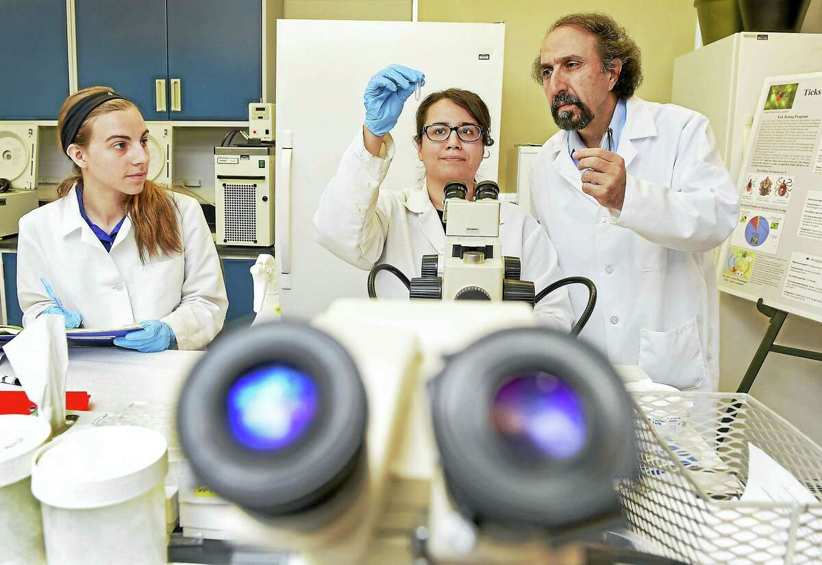 (Peter Hvizdak / Hearst Connecticut Media) Goudarz Molaei, a research scientist at the Connecticut Agricultural Experiment Station in New Haven and director of the State of Connecticut tick testing program right, in the tick testing lab at the experiment station with research assistants Kristina D'Agostino, left, and Mallery Breban, center, as they prepare to extract the DNA of a tick to identify the disease agent that it may carry. Molaei, an Associate Clinical Professor of Epidemiology at Yale University, has expertise in the areas of molecular biology, physiology, genetics, vector biology, epidemiology of vector-borne and zoonotic diseases.