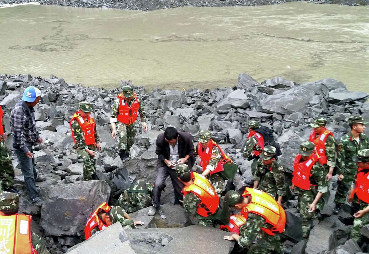 Emergency personnel and locals work at the site of a landslide in Xinmo village in Maoxian County in southwestern China's Sichuan Province, Saturday, June 24, 2017. Dozens of people are feared buried by a landslide that unleashed huge rocks and a mass of earth that crashed into their homes in southwestern China early Saturday, a county government said.