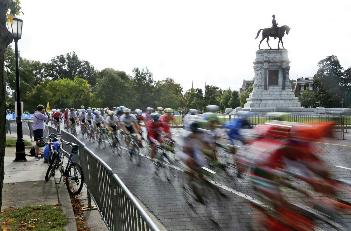 In this Sept. 27, 2015 file photo the peloton of the UCI Elite Men's Road World Championship passes by the statue of Confederate Gen. Robert E. Lee on Monument Avenue in Richmond, Va. Richmond Mayor Levar Stoney announced Thursday, June 22, 2017, the formation of a commission to help redefine the narrative of the statues on the avenue.