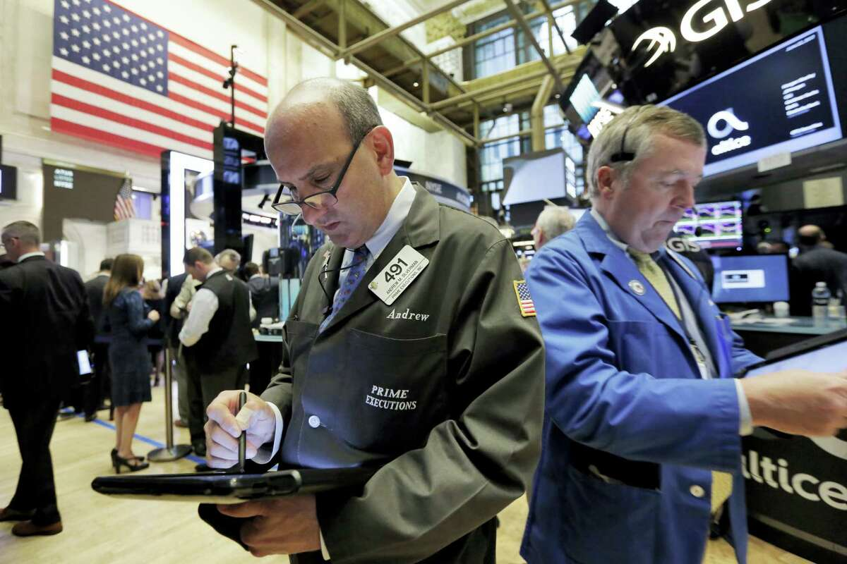 Traders Andrew Silverman, left, and James Lamb work on the floor of the New York Stock Exchange Thursday.