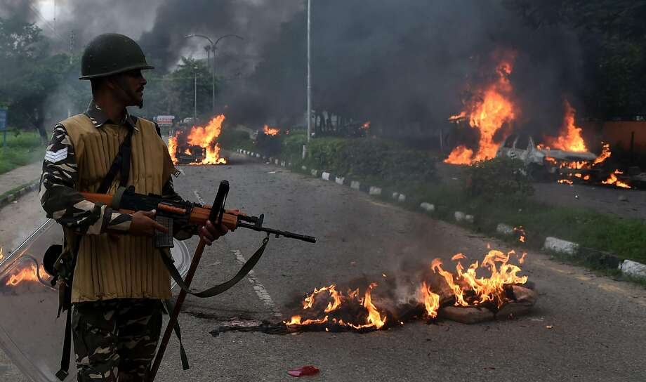 Security forces stand by the remnants of vehicles set on fire by followers of a quasi-religious sect leader. Photo: MONEY SHARMA, AFP/Getty Images