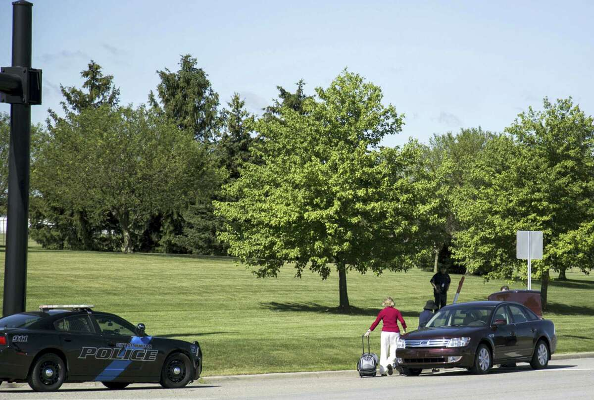 Travellers walk to a car outside Bishop International Airport, Wednesday morning, June 21, 2017, in Flint, Mich. Officials evacuated the airport Wednesday, where a witness said he saw an officer bleeding from his neck and a knife nearby on the ground. On Twitter, Michigan State Police say the officer is in critical condition and the FBI was leading the investigation.