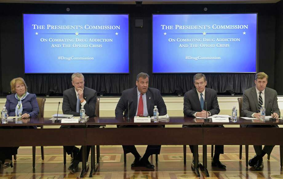 New Jersey Gov. Chris Christie, center, chairman of the President's Commission on Combating Drug Addiction and the Opioid Crisis, peaks at the beginning of the first meeting of the commission on combating drug addiction and the opioid crisis on June 16, 2017 in the Eisenhower Executive Office Building at the White House complex in Washington. From left are , Dr. Bertha K. Madras, a Harvard Medical School professor who specializes in addiction biology, Massachusetts Gov. Charlie Baker, Christie, North Carolina Gov. Roy Cooper, and former Rhode Island Rep. Patrick Kennedy. Photo: AP Photo — Susan Walsh  / Copyright 2017 The Associated Press. All rights reserved.