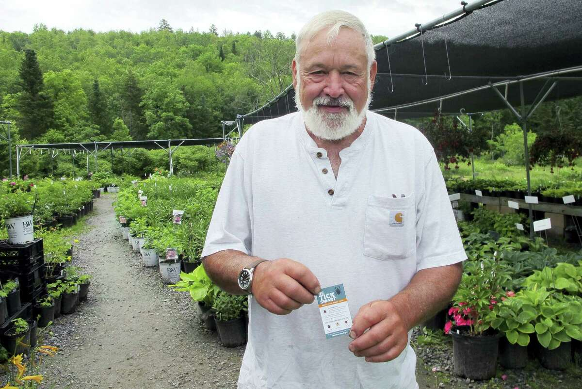In this June 19, 2017 photo, George Africa shows a state health department tick information card that he hands out to customers at his Vermont Flower Farm nursery in Marshfield, Vt., to educate them about ticks. Tick numbers are on the rise across New England this spring, raising the prospect of an increase in Lyme and other diseases.