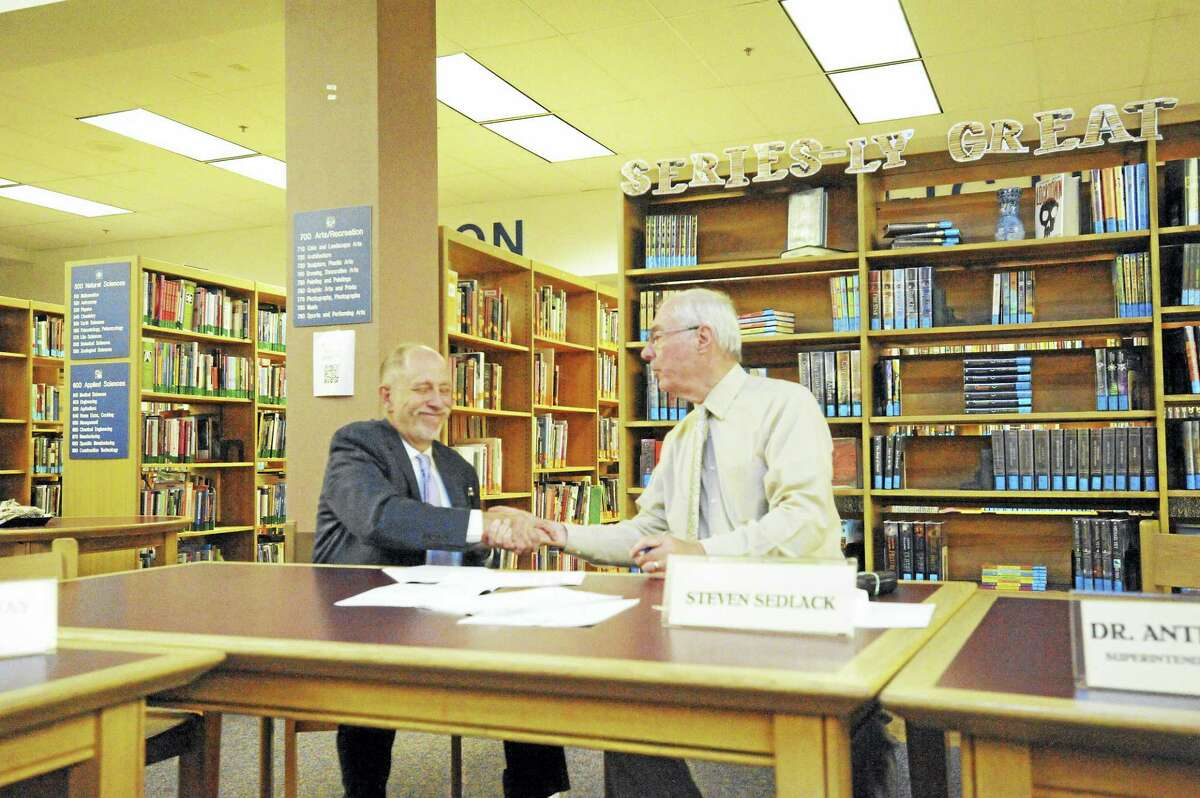 Receiver Freeman Burr and School Corp. Chairman Steven Sedlack shake hands after signing a new contract between The Gilbert School and the Winsted schools Tuesday.