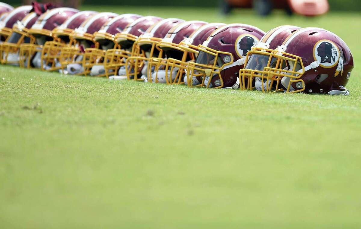 Washington Redskins football helmets are seen on the field during an NFL football team practice, Wednesday, June 14, 2017, in Ashburn, Va.