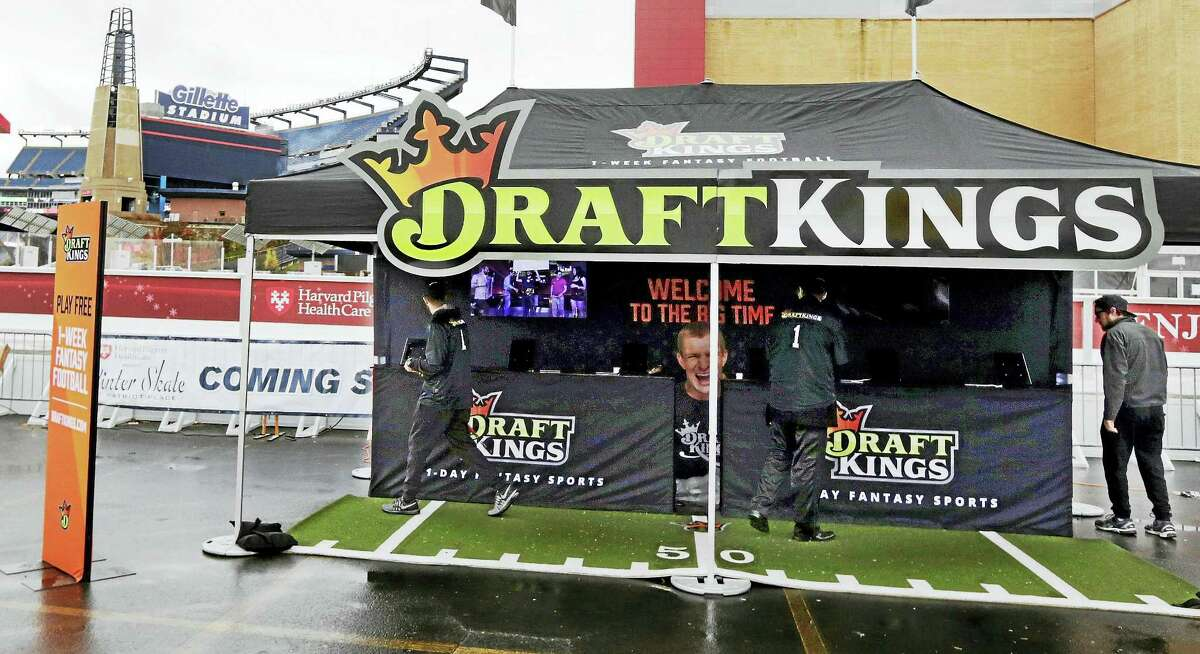 Workers set up a DraftKings promotions tent in the parking lot of Gillette Stadium, in Foxborough, Mass.