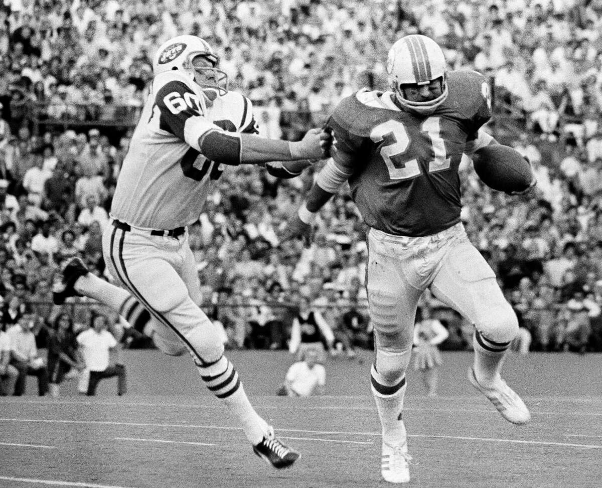 New York Jets linebacker Larry Grantham (60) catches Miami Dolphins back Jim Kiick (21), by the sleeve to throw him for a one-yard loss.