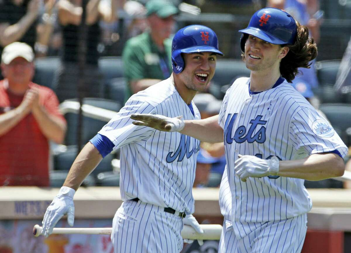 The Mets' Michael Conforto, left, congratulates starting pitcher Jacob deGrom, who hit a home run in the third inning on Sunday.