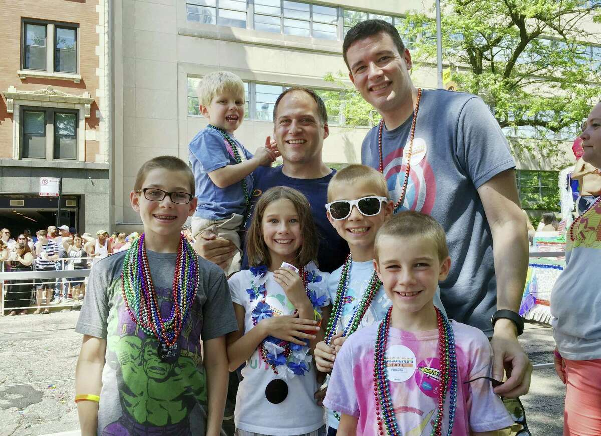 This June 26, 2016 photo provided by the family shows Kevin Neubert, background center, and Jim Gorey with their adopted children, from left, Luke, Derek, Natalie, Zach, and Jacob at the Chicago Pride Parade. Following night classes to qualify as foster parents, Neubert and Gorey agreed in December 2011 to provide a temporary home for a newborn baby. A stay intended to last only for a few days was extended into several months, and Neubert and Gorey learned that the baby had four older siblings who were also in foster care.